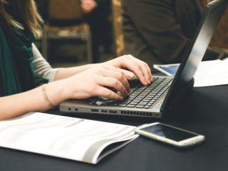 Kvinde skriver på computer med noter