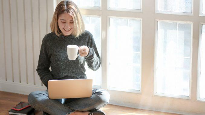 Kvinde drikker kaffe imens hun er på computeren