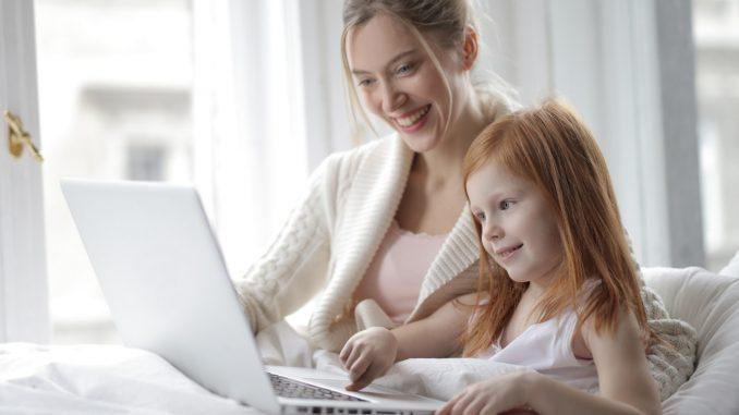 Mor og datter griner af noget på computeren