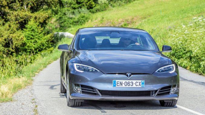 Tesla kører på landevej i naturen