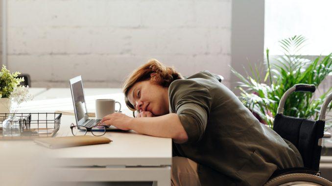 Kvinde er træt og ligger ved sin computer