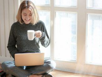 Kvinde i gråt drikker kaffe imen hun er på computeren