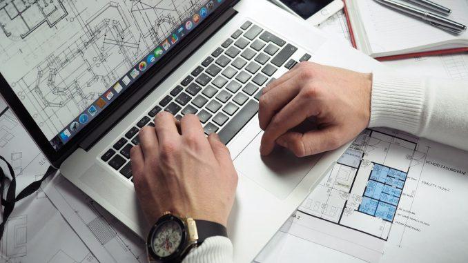 Mand designer arkitektur på sin computer