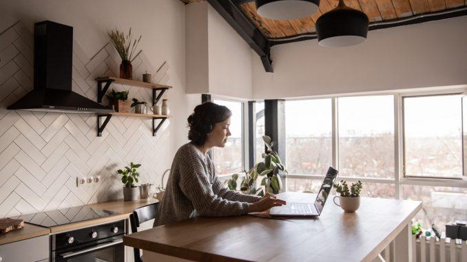 Kvinde står i køkkenet og taster på hendes tastatur