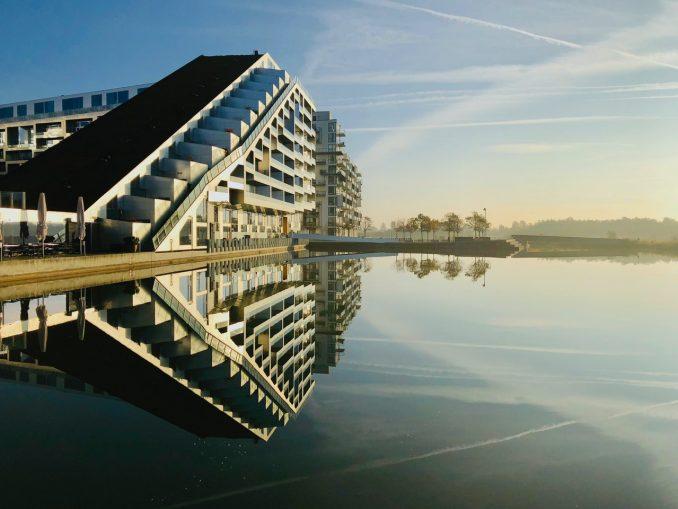 Stort boligkompleks ud til vandet med solnedgang